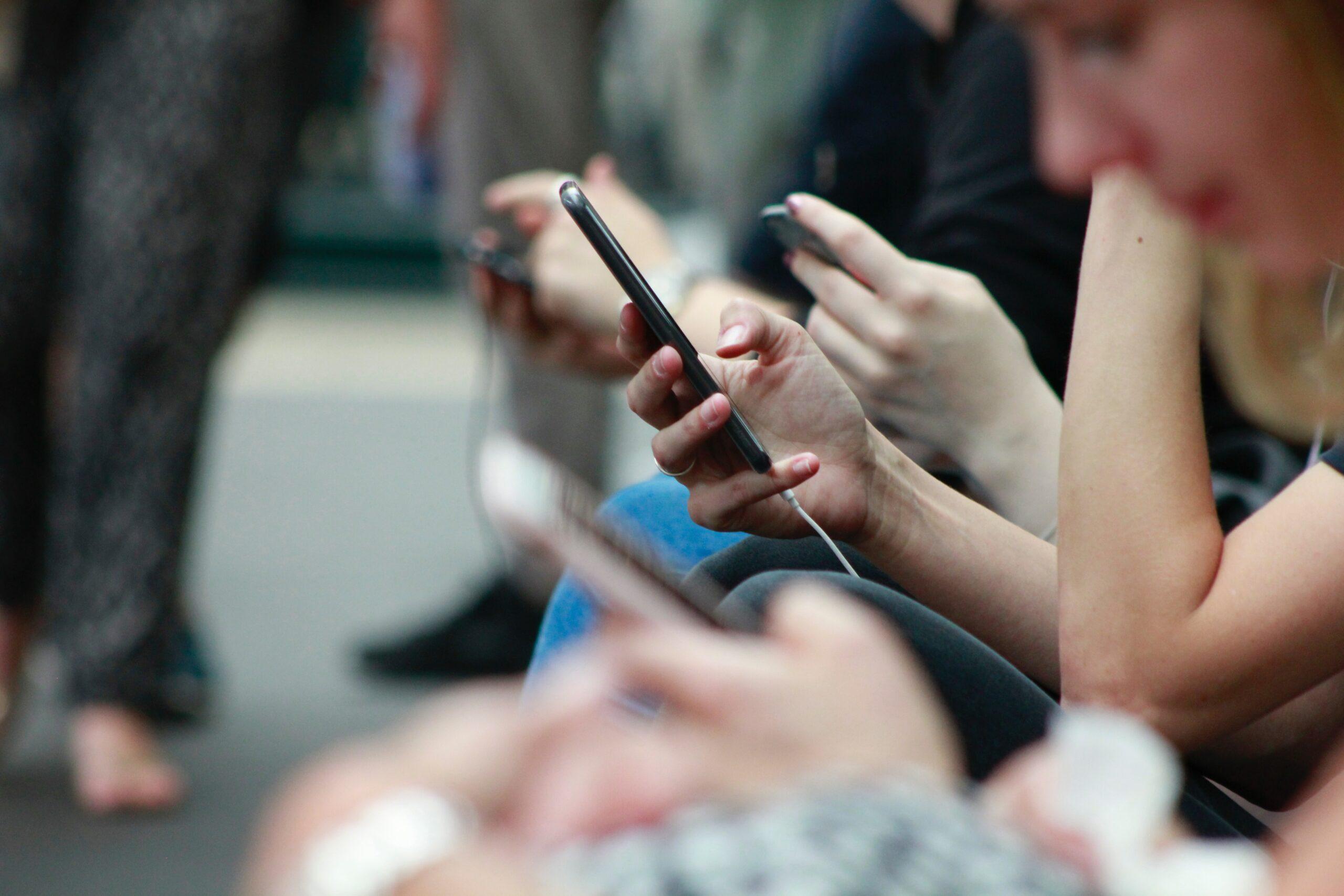 People n their phones reading social media