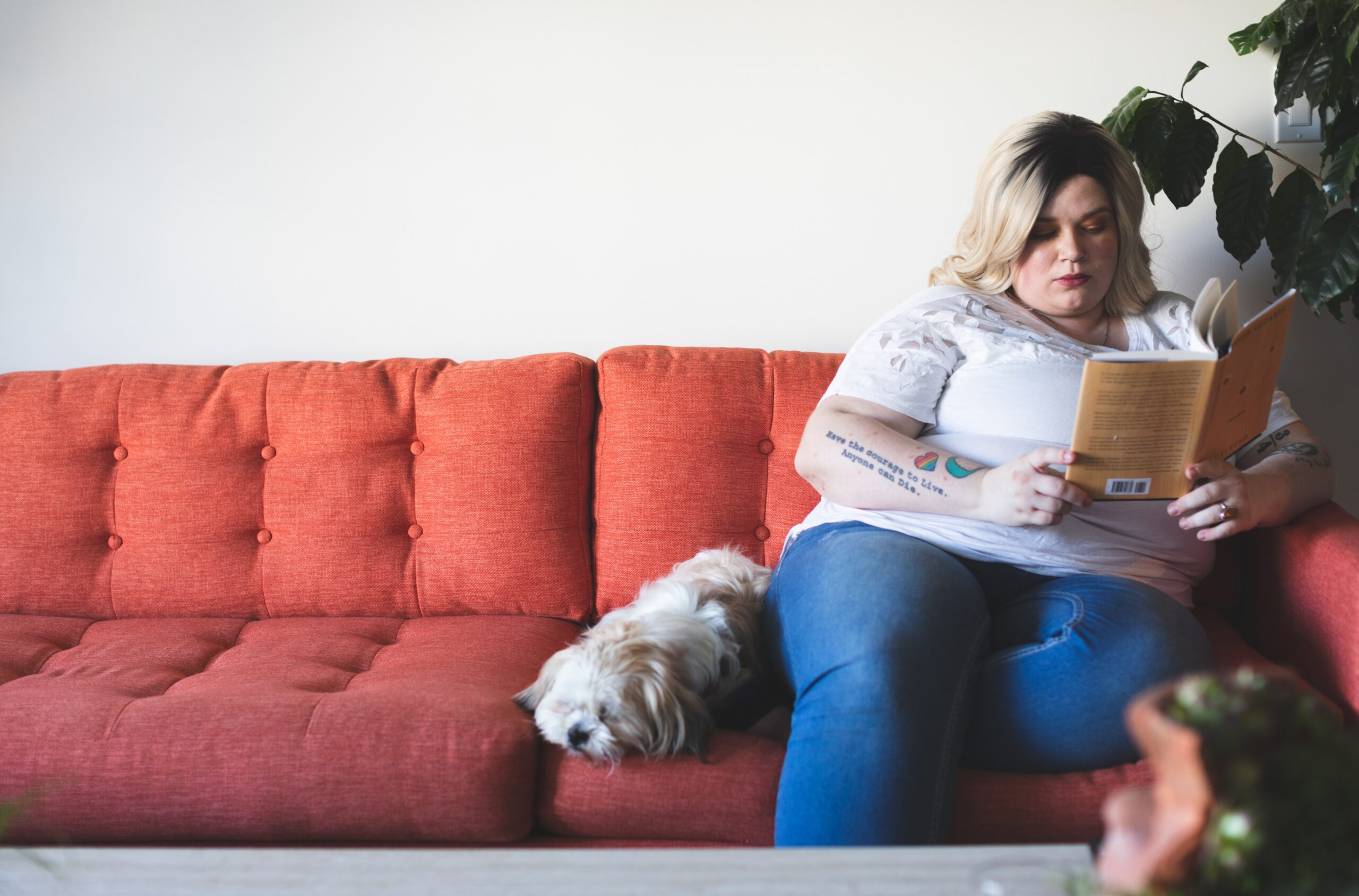Larger blond woman sitting on a couch reading a book