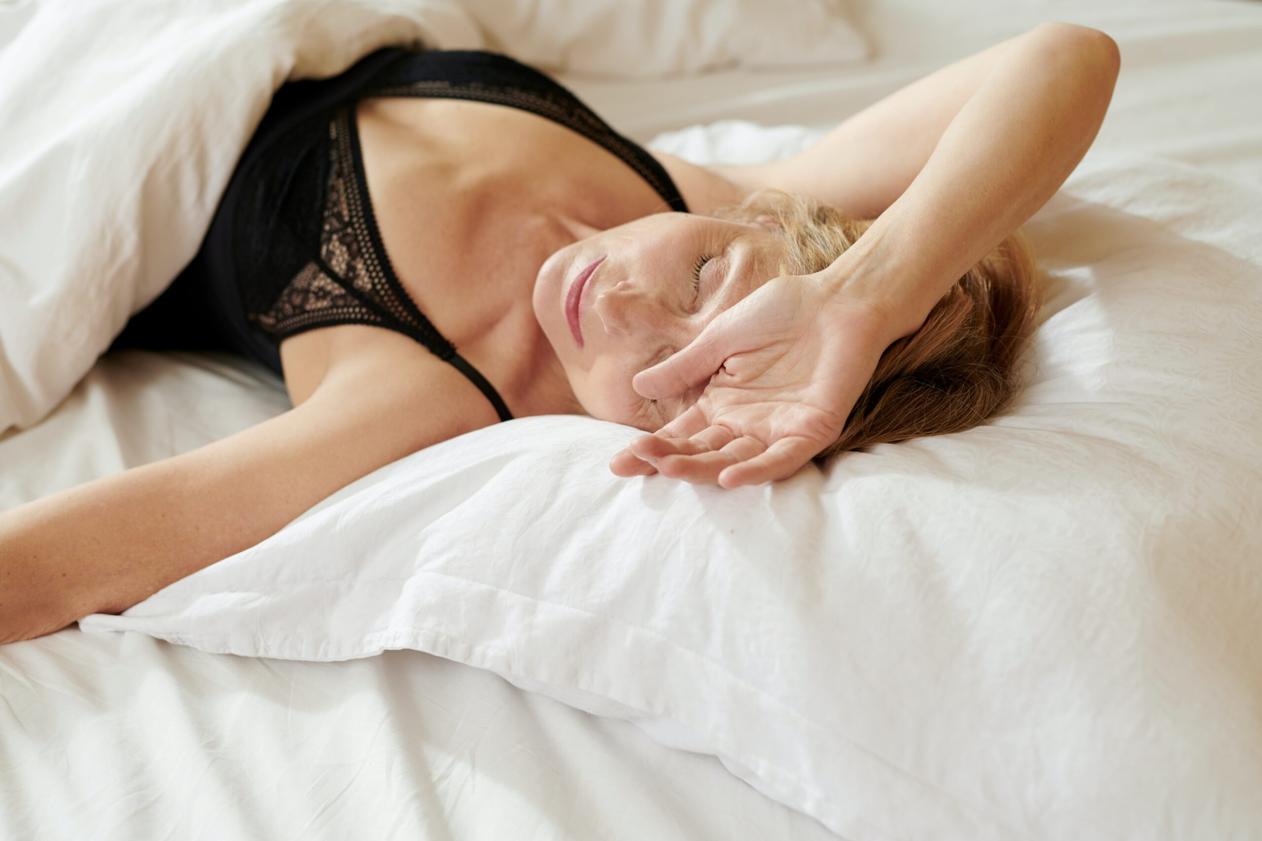 woman layin gin bed with just bra and arm over her face