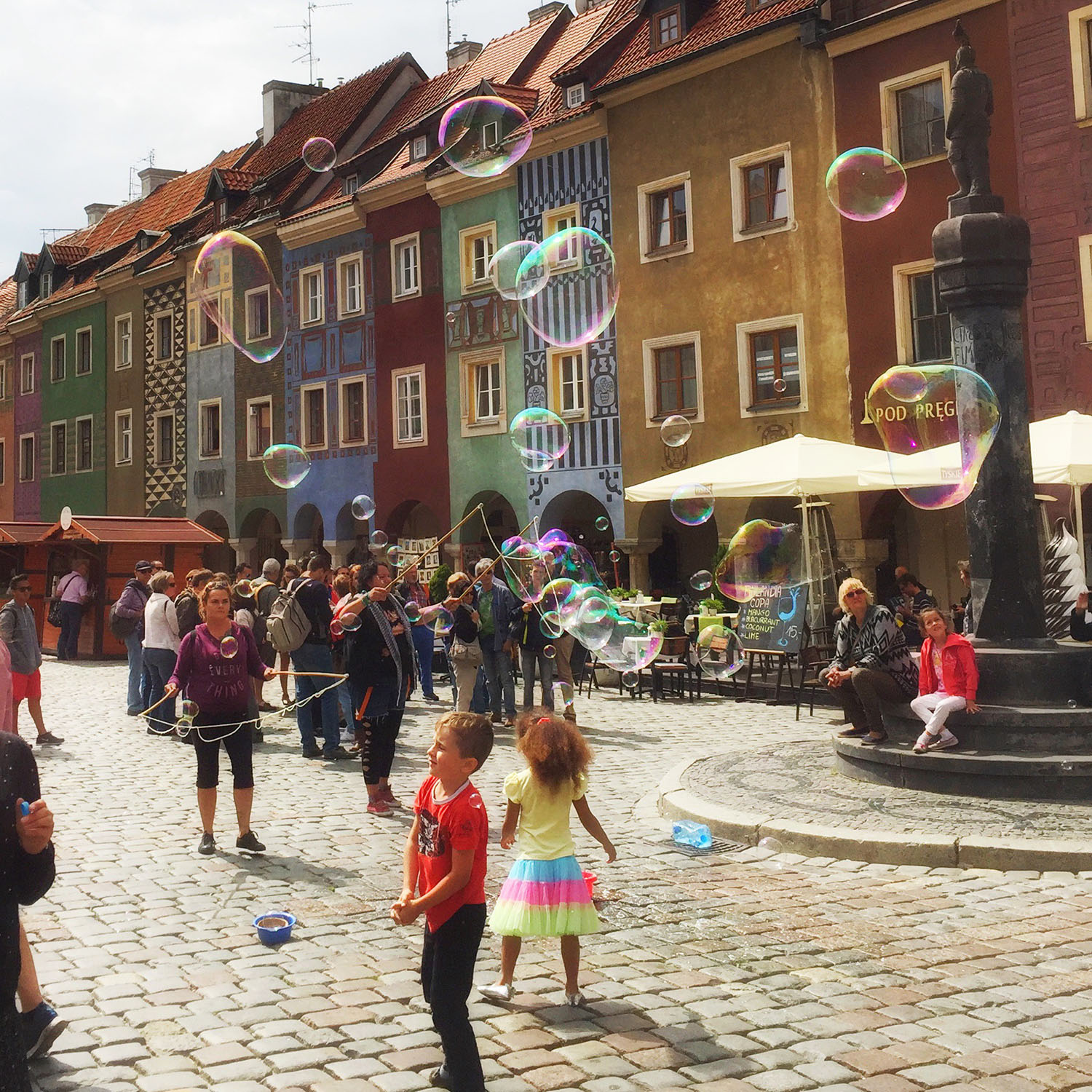 Children playing with bubbles in front of colorful buildings