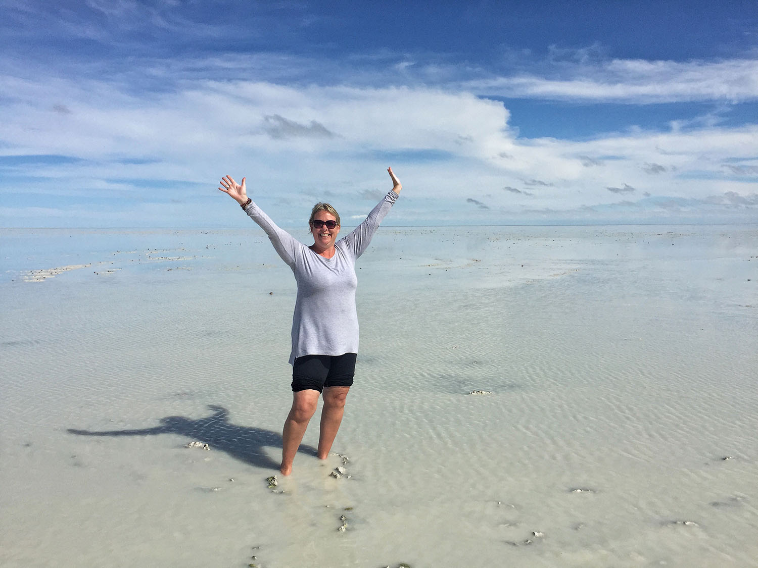 me with my arms raised standing in the salt pan in Botswana