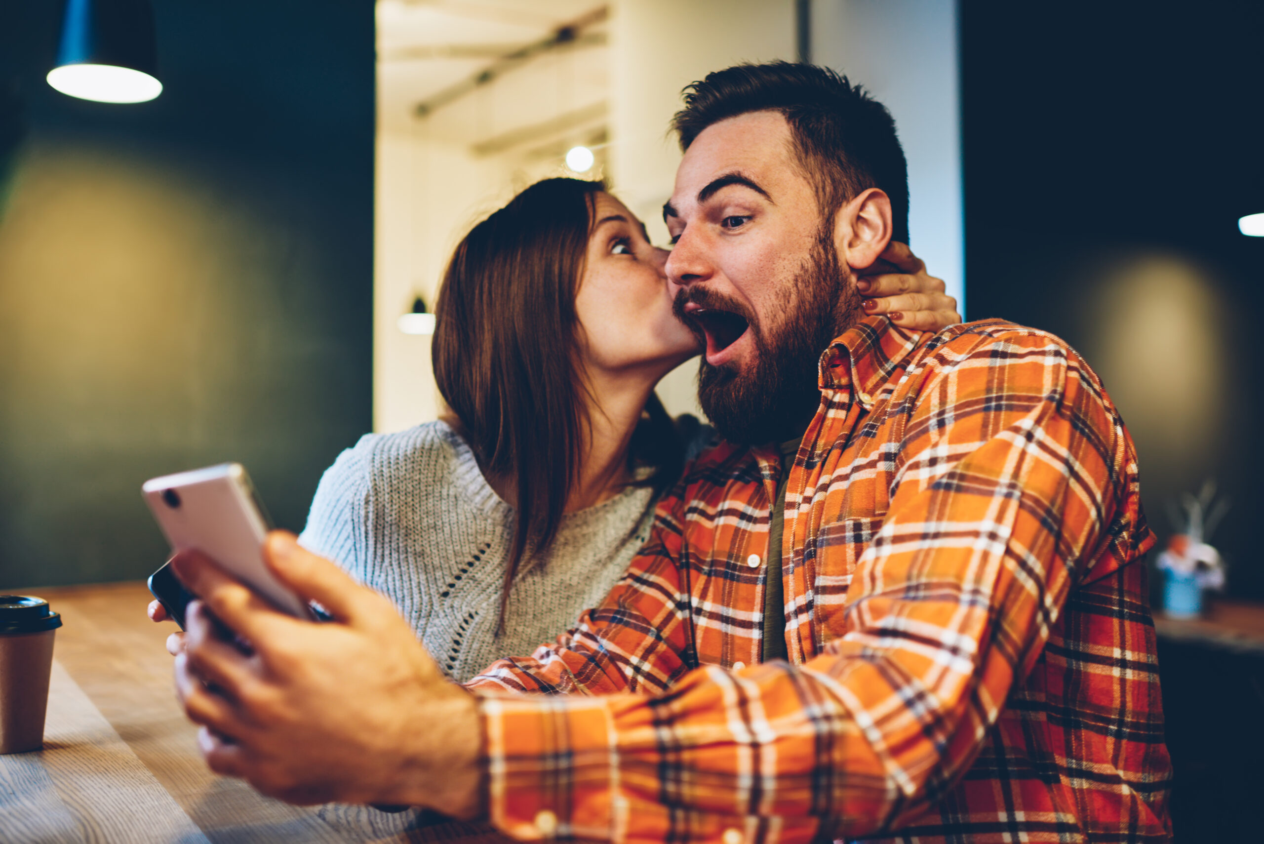 Happy young woman kisses her bearded boyfriend who won prize in internet lottery.Amazed coung couple in love rejoices in victory in online contest on smartphone device sitting at home interior