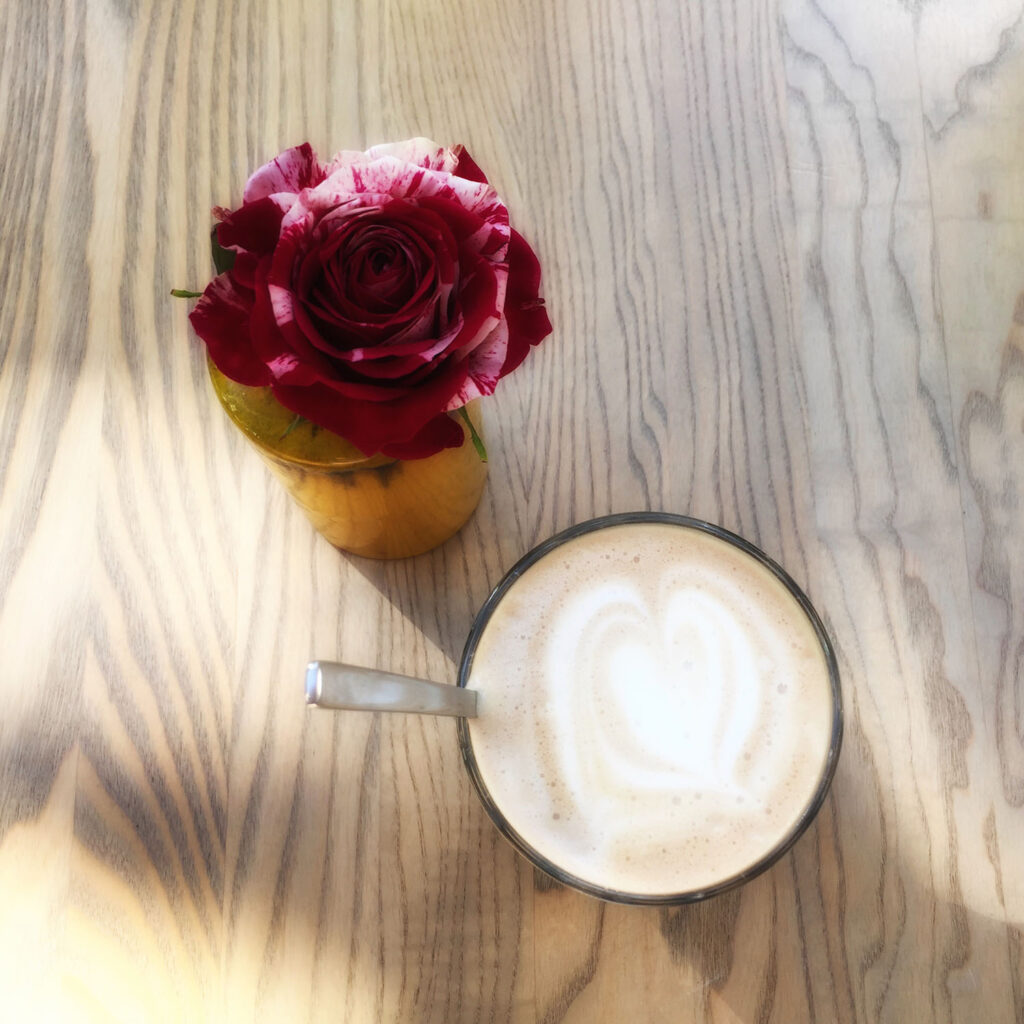 latte with a white foam sitting nest to a pretty purple flower on a wooden table