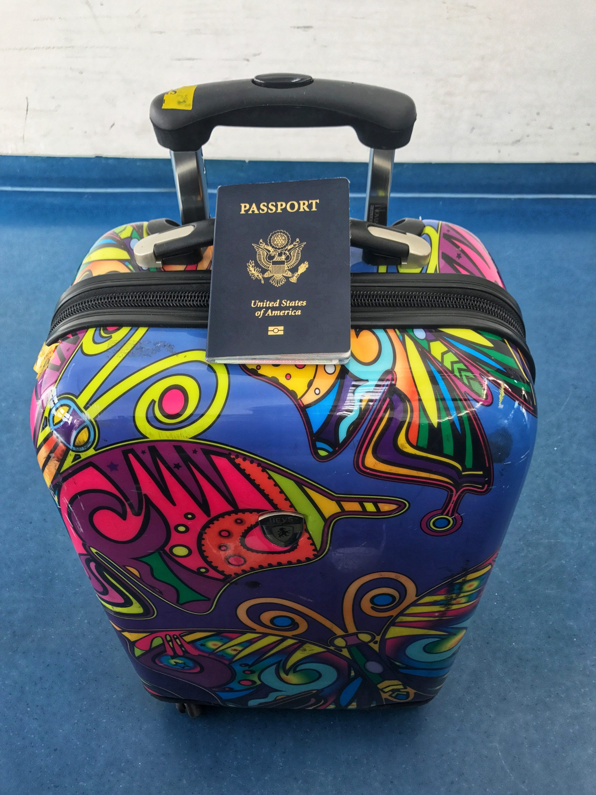 Colorful carry-on suitcase with passport on top of it