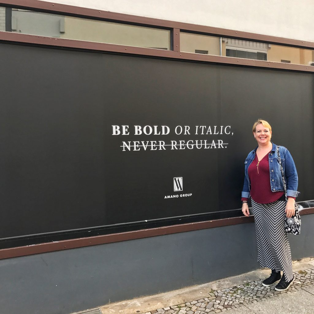 """Along woman wearing a red tunic top over a black and white striped long skirt, black high top sneakers, a denim jacker and black and white floral bag in front of a sign that says """"Be Bold or Italic- Never Normal"""""""