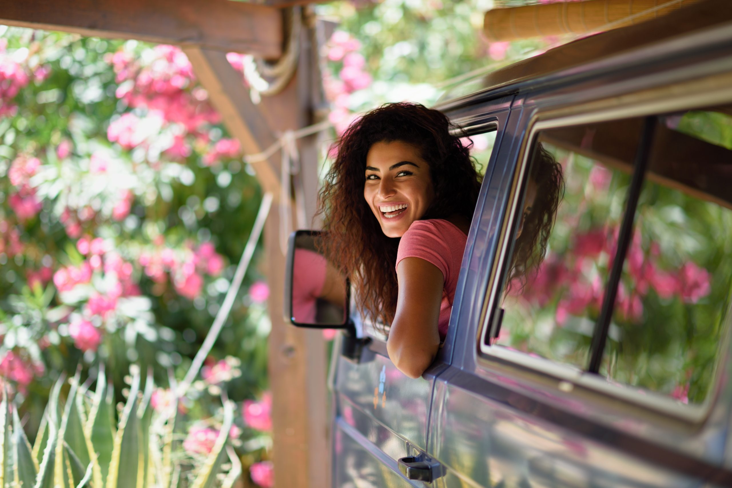 Young woman in a camper van enjoying spring time in a beautiful camping with pink flowers.