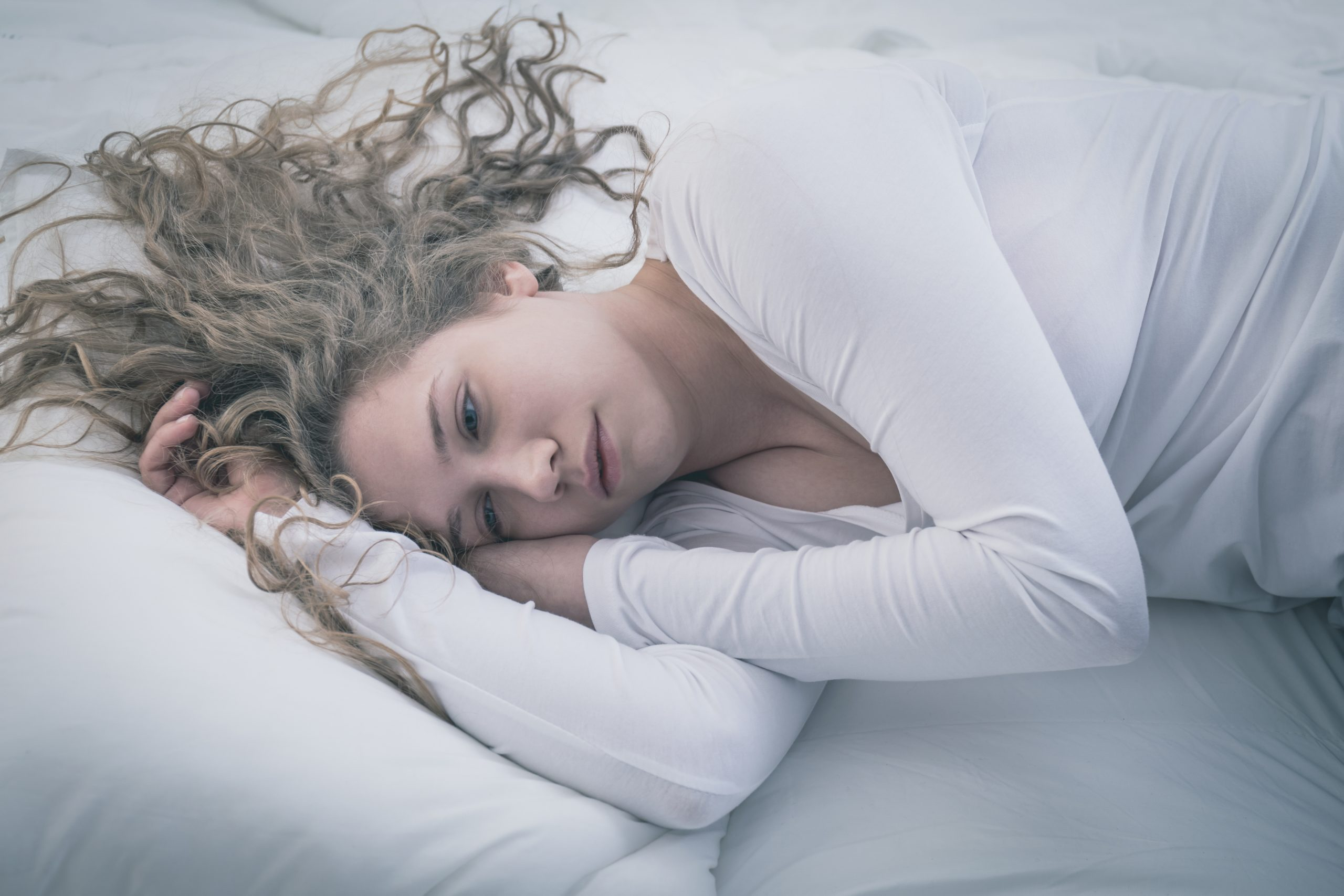 Young blond woman with curly hair wearing white in deep depression lying alone